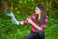 Eine junge Frau betrachtet eine Karte beim Wandern Lizenzfreies Stockbild