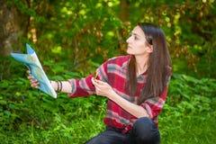 Eine junge Frau betrachtet eine Karte beim Wandern Stockfotos
