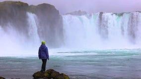 Eine junge Frau bewundert einen starken rasenden Wasserfall, der schwer entlang einen felsigen Rand fällt Auf dem Felsen fällt ei stock video footage