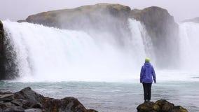 Eine junge Frau bewundert einen starken rasenden Wasserfall, der schwer entlang einen felsigen Rand fällt Auf dem Felsen fällt ei stock footage