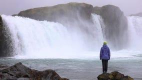 Eine junge Frau bewundert einen starken rasenden Wasserfall, der schwer entlang einen felsigen Rand fällt Auf dem Felsen fällt ei stock video