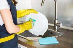 Eine junge Frau in den gelben Handschuhen w?scht Teller mit einem Schwamm in der Wanne Hausberufsreinigungsservice lizenzfreies stockfoto