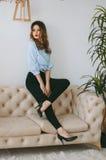 Eine junge Frau in den Kojen und in einem Hemd, Fersen auf ihren Fersen, die auf der Rückseite der Couch sitzen Stockbilder