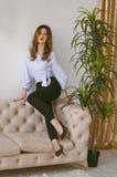 Eine junge Frau in den Kojen und in einem Hemd, Fersen auf ihren Fersen, die auf der Rückseite der Couch sitzen Stockbild