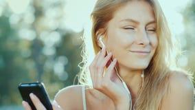 Eine junge Frau in den Kopfh?rern h?rt Musik, benutzt einen Smartphone Die Sonne belichtet sch?n ihr Haar stock video footage