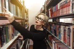 Eine junge Frau in der Bibliothek wählt ein Buch Lizenzfreie Stockfotos