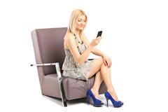 Eine junge Frau, die auf einem Stuhl sitzt und an einem Handy spricht Stockbilder