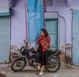 Eine junge Frau, die auf Motorrad sitzt lizenzfreie stockfotos
