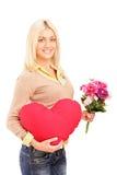 Eine junge Frau, die Blumen und rotes Inneres anhält Stockbild