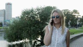 Eine junge Frau, die in den Park geht und am Telefon spricht Langsame Bewegung stock footage