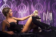 Eine junge Frau, die in der sexy Wäsche mit einem Schädel aufwirft Lizenzfreie Stockfotos