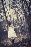 Junge Frau, die in unfruchtbaren Wald geht Stockbild