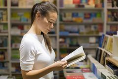 Eine junge Frau, die ein Buch in der Bibliothek liest lizenzfreie stockfotografie