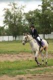 Eine junge Frau, die ein Pferd reitet Lizenzfreies Stockfoto