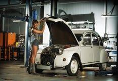 Eine junge Frau, die ein Retro- Auto in einer Garage repariert lizenzfreie stockbilder