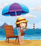 Eine junge Frau, die eine Eiscreme am Strand isst Stockbilder