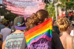 Eine junge Frau, die eine homosexuelle Regenbogenflagge hält lizenzfreie stockfotos