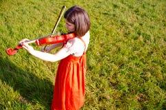 Eine junge Frau, die eine Violine in der Natur spielt Lizenzfreies Stockbild