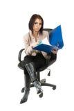 Eine junge Frau, die in einem Bürolehnsessel sitzt Lizenzfreies Stockfoto