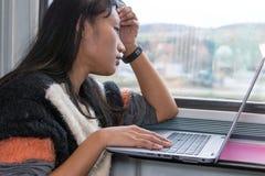 Eine junge Frau, die an einem Computer auf einem Zug arbeitet stockfoto