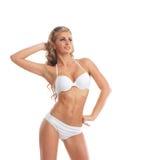 Eine junge Frau, die in einem weißen Badeanzug aufwirft Lizenzfreie Stockfotos
