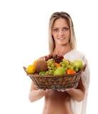 Eine junge Frau, die einen Korb voll von den Früchten anhält Lizenzfreie Stockfotografie
