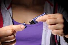 Eine junge Frau, die einen USB-Flash-Speichersteuerknüppel anhält Lizenzfreie Stockfotos