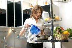Eine junge Frau, die in einer modernen Küche kocht Lizenzfreie Stockfotografie
