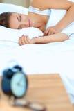 Eine junge Frau, die ihren Wecker morgens verschiebt lizenzfreies stockbild