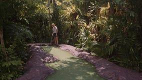 Eine junge Frau, die Minigolf spielt stock footage