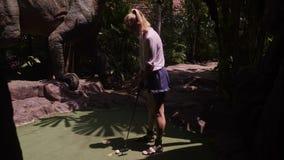 Eine junge Frau, die Minigolf spielt stock video
