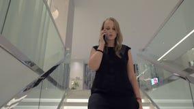 Eine junge Frau, die mit einem Smartphone beim die Treppe hinunter gehen spricht stock video footage