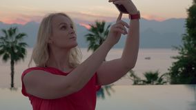 Eine junge Frau, die selfies durch die schöne Glättungslandschaft nahe dem Pool nimmt stock footage