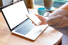 Eine junge Frau, die Smartphone und Laptop im Café verwendet stockfoto