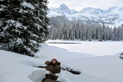 Eine junge Frau, die Spaß um Island See in Fernie, Britisch-Columbia, Kanada hat Der majestätische Winterhintergrund ist hübsch lizenzfreie stockfotografie