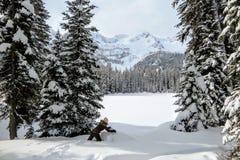 Eine junge Frau, die Spaß um Island See in Fernie, Britisch-Columbia, Kanada hat Der majestätische Winterhintergrund ist wunderba lizenzfreie stockfotografie