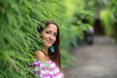 Eine junge Frau, die Stellung in einer Hecke des Grases, Nahaufnahme aufwirft lizenzfreie stockbilder