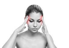 Eine junge Frau, die unter den Schmerz im Kopf leidet stockbild