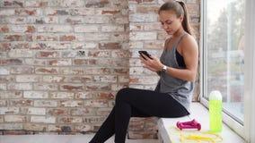 Eine junge Frau, die vor kurzem Sportkontrollsoziale netzwerke in ihrem Telefon aufnahm stock video