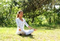 Eine junge Frau, die Yoga in einem grünen Wald tut Lizenzfreies Stockfoto