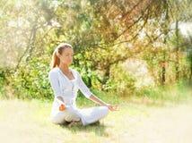 Eine junge Frau, die Yoga in einem grünen Wald tut Stockfoto