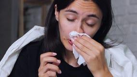 Eine junge Frau, die zu Hause auf dem Bett, Kranker, seine Nase in einem Taschentuch durchbrennend sitzt stock video footage