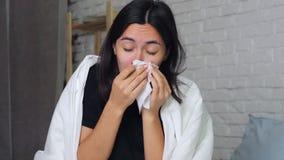Eine junge Frau, die zu Hause auf dem Bett, Kranker, seine Nase in einem Taschentuch durchbrennend sitzt stock footage