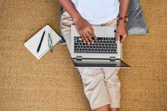 Eine junge Frau, die zu Hause an einer Laptop-Computer arbeitet Geschäftsbetrug stockfotos