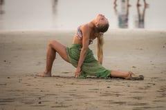 Eine junge Frau in einem Bikini nimmt an Yoga auf dem Strand teil Lizenzfreie Stockbilder