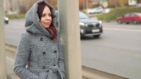 Eine junge Frau in einem grauen Mantel stock video
