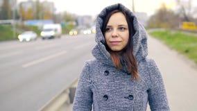 Eine junge Frau in einem grauen Mantel stock footage
