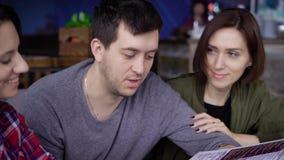 Eine junge Frau in einem Hemd, ein Mann in einer Strickjacke und eine Frau, die in einer Windjacke und in einem T-Shirt gekleidet stock footage