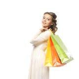 Eine junge Frau in einem Kleid, das Einkaufstaschen hält Stockfotografie