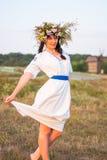 Eine junge Frau in einem langen Weiß stickte Hemd und in einem Kranz Stockfotografie